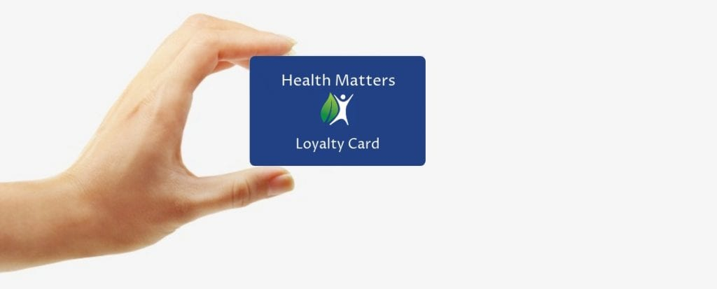 Hand holding Health Matters loyalty card beside text sign up for great discounts